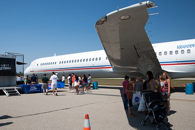 People getting out of the sun underneath the Detroit Piston's airplane