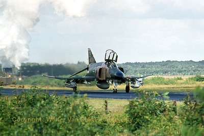 """A F-4E Phantom II in Vietnam-type c/s - on a wet taxiway - at Soesterberg AFB during the late seventies. This aircraft is equipped with TISEO -Target Identification System Electro Optical (big lens visible on the leading edge of the left wing). It also carries a """"dart"""" - under the left wing - as a target -tug (A2A-shooting). Scan from slide."""