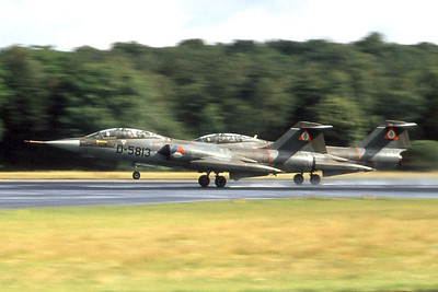 Formation take-off of two Dutch twin-sticks TF-104G (D-5813, cn 583E-5813), on a wet runway at Soesterberg during the late seventies. Scanned from slide