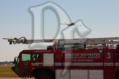 The Genesee Warbirds CM-170 flies over Airport Fire Department Rescue 3 during the 2011 ESL International Airshow in Rochester, NY.
