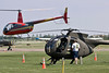 A Hughes OH-6 in the foreground, with a Robinson R44 (red helicopter) lifting off and a Yak-52 taxiing from the left.