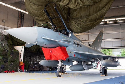 "This German Air Force twin-stick Eurofighter EF-2000 Typhoon T (30+04; cn018/GT004), could be seen in one of the hangars of Nörvenich, during the spottersday, prior to the ""Tag der Bundeswehr""."