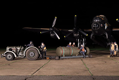 "AVRO 683 Lancaster B7 ""Just Jane"" (G-ASXX; NX611/DX-F/LE-H), seen here with some re-enactors during a night photoshoot at the Lincolnshire Aviation Heritage Centre, East Kirkby, simulating the loading of a 8000lb High Capacity Bomb. [TimeLine Events & COAP]"