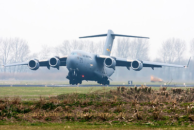 USAF C-17A (07-7184; P187) from 437th AW/315th AW, rotates at the end of RWY23 on her departure from Leeuwarden Air Base, on a grey and dull morning.