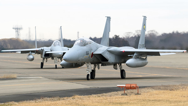 "On a very cold winter morning, two JASDF F-15J's depart for another training sortie. F-15J (22-8936; cn136) from 306 Hikotai (Golden Eagle), is seen here on the taxiway at Hyakuri in front of his wingman F-15J (42-8947; cn147). The 306th Tactical Fighter Squadron is a squadron of the 6th Air Wing of the Japan Air Self-Defense Force, based at Komatsu Air Base, in Ishikawa Prefecture, Japan. The squadron's aircraft carry a golden eagle as their tail marking, inside a stylized ""6"" indicating the 6th Air Wing. The golden eagle can be found in the mountains near Komatsu air base, and is also the prefectural bird of Ishikawa."