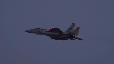 three F-15s taking off at dusk