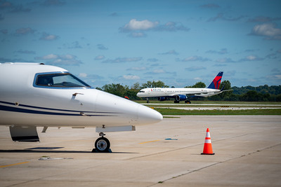 Delta 757 taxiing past a Learjet
