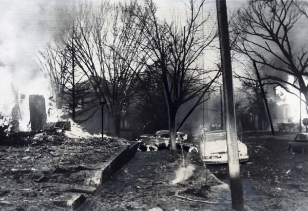 This house on Maryland Street was struck by portions of the bomber and set ablaze.  Fire also destroyed the 1953 Mercury behind the tree in the background.  (UPI Photo)