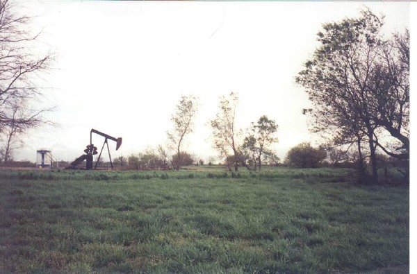 In the years since the crash, wreckage would turn up when the field was plowed for crops.  Later, an oil well was drilled and a pump jack and tank were installed over the crash site.