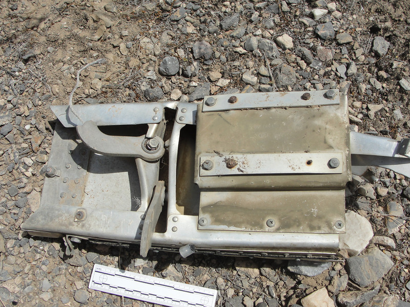 Other side of the piece has two hinge arms which supported the armament bay doors.  The wire that seems to protrude from the upper hinge is a bonding wire that would have attached to the door.  You can see the broken remnant of the other door's wire to the left of the lower hinge arm.