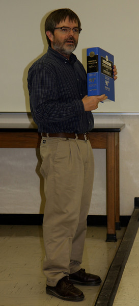 Dr. Cox holds up the CRC Handbook as part of the award for the Outstanding Freshman Chemistry Award.