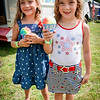From left, Sophia Mercier, 6, and her twin Toni of Leominster enjoy a cold snowcone on a hot day after the Ayer 4th of July Parade. SUN/Caley McGuane
