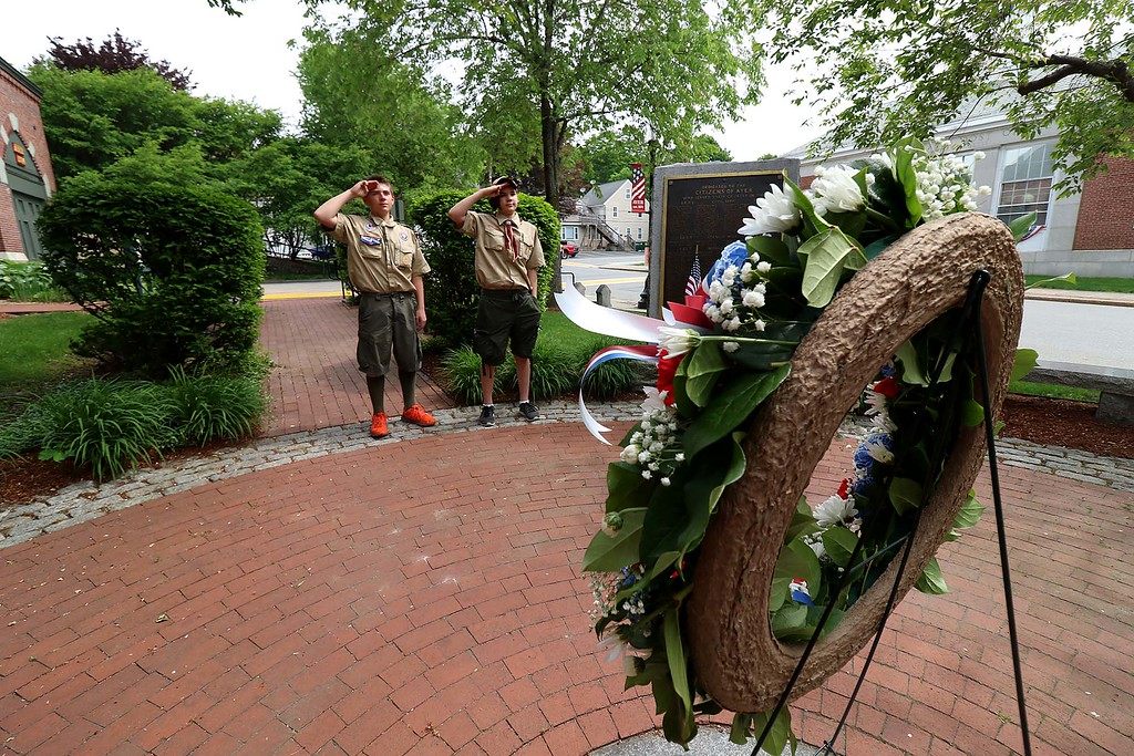 . The Town of Ayer held its Memorial Day parade and ceremony on Saturday May 26, 2018. The Parade went down Park Street to Main Street and stop for a ceremony at Town Hall. After that they went on to the Pirone Park where a wreath was thrown into Grove Pond. Boy Scouts Graham Wall from Troop 3 and Jamie Carney from Troop 2 salute as taps is played after placing a wreath at the monuments at Town Hall. SENTINEL & ENTERPRISE/JOHN LOVE