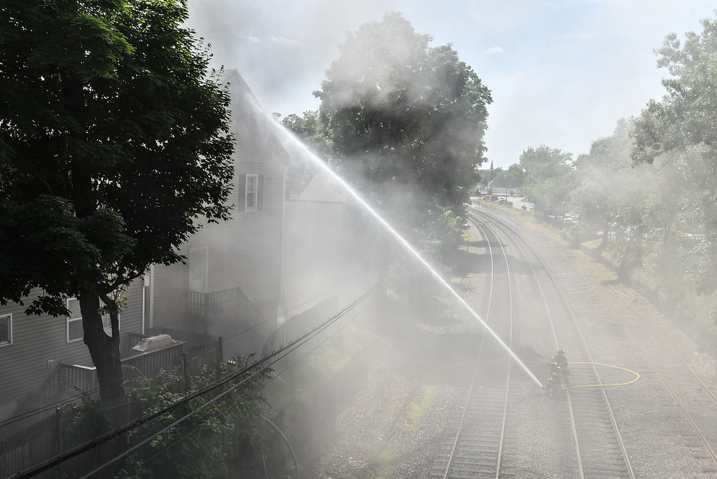. Firefighters use water from the railroad tracks at a structure fire on 10 East Main St. in Ayer on Sunday.  SENTINEL & ENTERPRISE JEFF PORTER