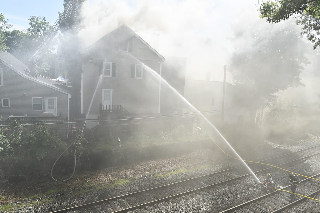 . Firefighters from surrounding town\'s assist with a structure fire from multiple angles on 10 East Main St. in Ayer on Sunday.  SENTINEL & ENTERPRISE JEFF PORTER