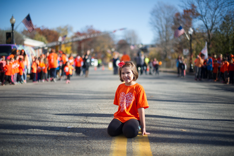 Kendall Farnsworth, 7, daughter of dance organizer Karyn Farnsworth, sits on the ground just as the dance was about to begin in downtown Ayer on Sunday for a global freezemob/flashmob celebration dance for kindness which was performed in front of Ayer Town Hall.  Sentinel & Enterprise photo/Jeff Porter