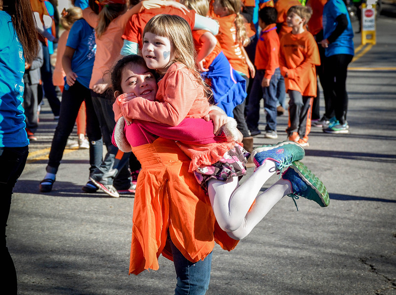 From left, Belladonna Quinn, 6, of Ayer hugs and lifts up Rose Floyd, 7, of Ayer after both dancing in the Kindness Flashdance. SUN/Caley McGuane