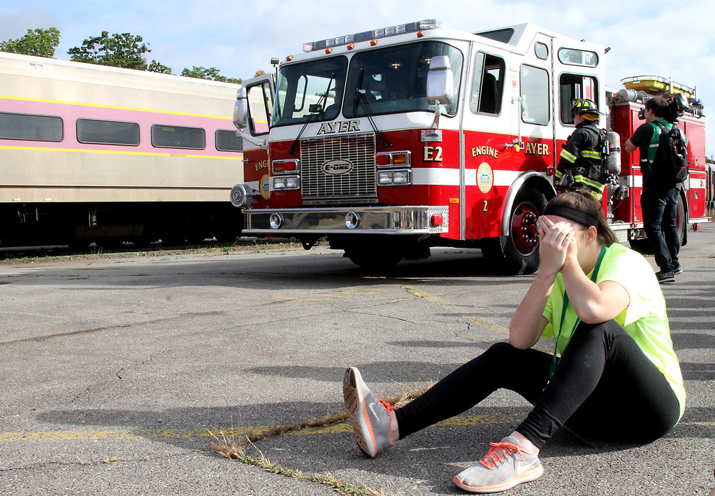 . Mock train crash victim, Nicole Patterson,22 of Littleton reacts as firefighters arrive at the scene in the PanAm railroad yard in Ayer. Nashoba Valley Voice Photo by David H. Brow