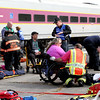 Firefighters and emt's tend to a mock train crash victim in a wheelchair. Nashoba Valley Voice Photo by David H. Brow