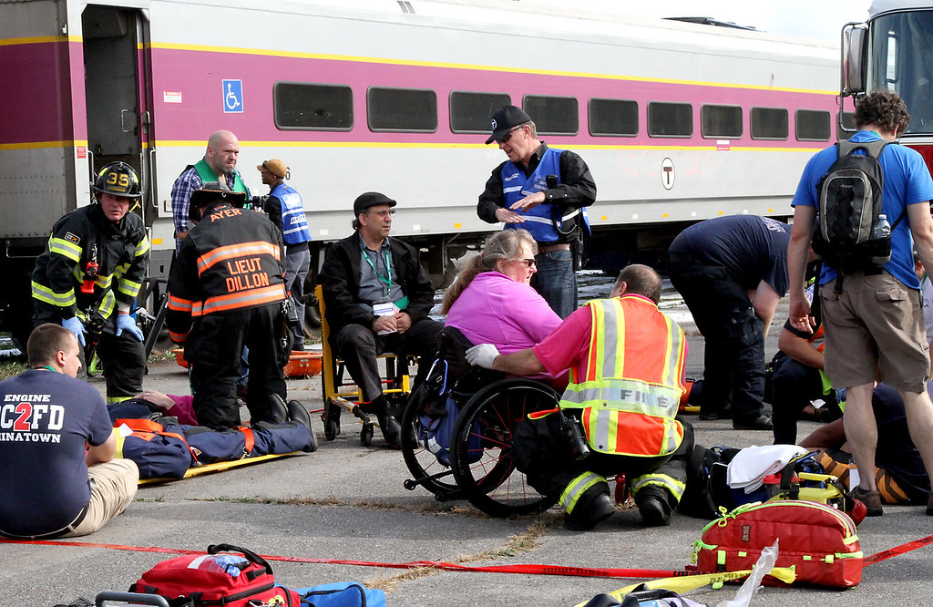 . Firefighters and emt\'s tend to a mock train crash victim in a wheelchair. Nashoba Valley Voice Photo by David H. Brow