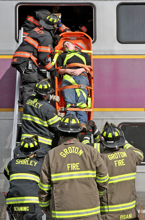 . Firefighters from Shirley and Groton take out mock train crash victim, Brian Smith, 15 of Boxboro, from the 2nd story window of a double decker commuter train. Nashoba Valley Voice Photo by David H. Brow