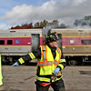 Mock train crash victim, Nicole Patterson,22 of Littleton(on left) is led away from the burning train as firefighters arrive at the scene in the PanAm railroad yard in Ayer. Nashoba Valley Voice Photo by David H. Brow