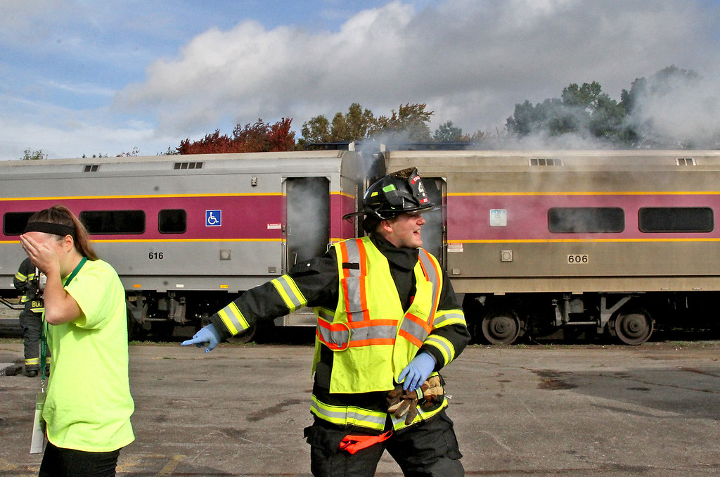. Mock train crash victim, Nicole Patterson,22 of Littleton(on left) is led away from the burning train as firefighters arrive at the scene in the PanAm railroad yard in Ayer. Nashoba Valley Voice Photo by David H. Brow
