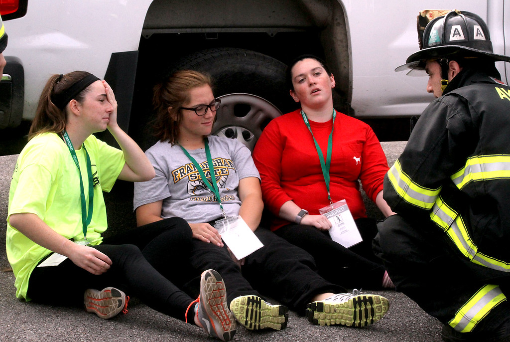 . Mock train crash victims L-R, Nicole Patterson,22, Meaghann Ackerman,20 and her sister Ashley Ackerman,23, all from Littleton, speak with a Ayer FF to relay their injuries. Nashoba Valley Voice Photo by David H. Brow