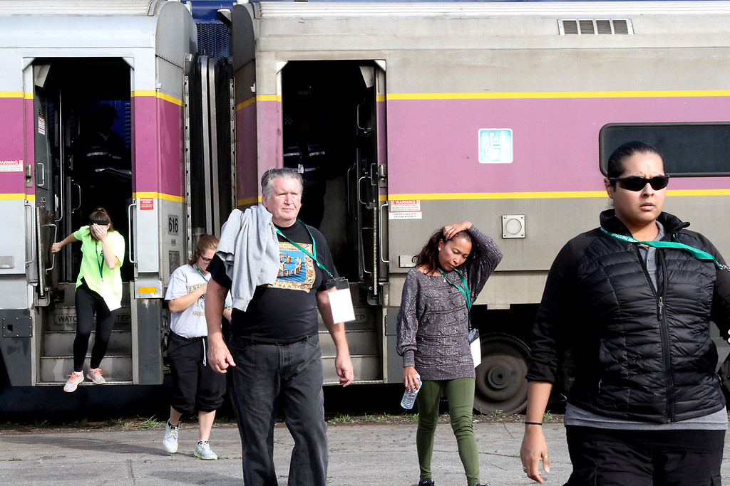 . Victims exit a commuter train after a mock crash in the PanAm railroad yard in Ayer. Nashoba Valley Voice Photo by David H. Brow