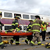 Firefighters from Shirley and Groton remove mock train crash victim, Brian Smith, 15 of Boxboro, after getting him from the 2nd story window of a double decker commuter train. Nashoba Valley Voice Photo by David H. Brow