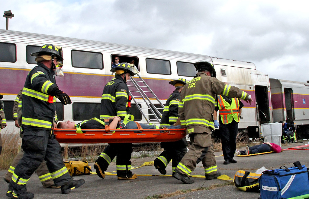 . Firefighters from Shirley and Groton remove mock train crash victim, Brian Smith, 15 of Boxboro, after getting him from the 2nd story window of a double decker commuter train. Nashoba Valley Voice Photo by David H. Brow
