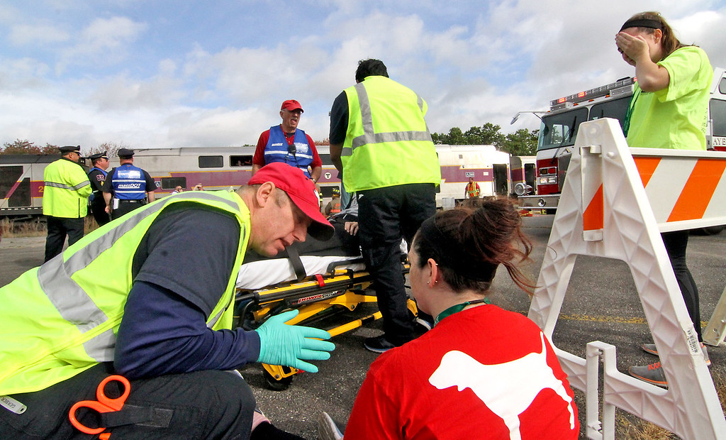 . Harvard EMT Chris Mitchell talks to mock train crash victim Ashley Ackerman,23 of Littleton at the PanAm railroad yard in Ayer. Nashoba Valley Voice Photo by David H. Brow