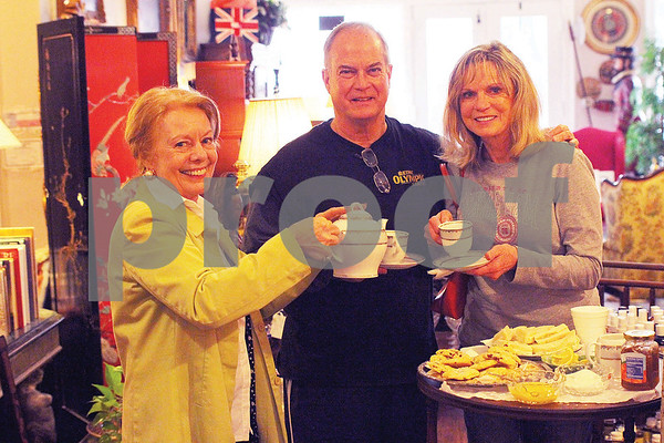 Dorothy Ferguson, owner of the Carriage House Gallery, in the Brick Street Village, pours tea for Betty Paul and Gary Steinbach, of Tyler, while hosting a tea party for visitors to the Azalea and Spring Flower Trail on Saturday, March 21, 2015. (Cory McCoy/Staff)