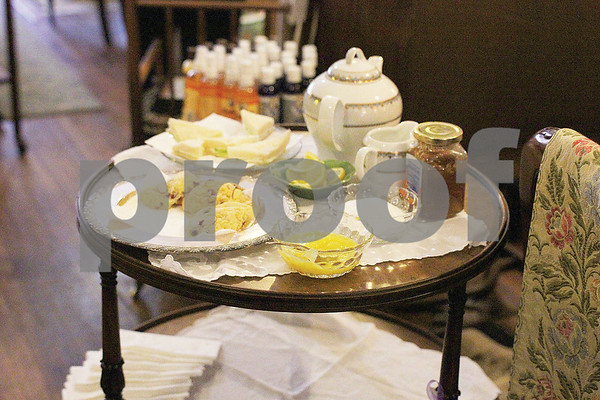 Dorothy Ferguson, owner of the Carriage House Gallery, in the Brick Street Village, hosts a tea party for visitors to the Azalea and Spring Flower Trail on Saturday, March 21, 2015. (Cory McCoy/Staff)