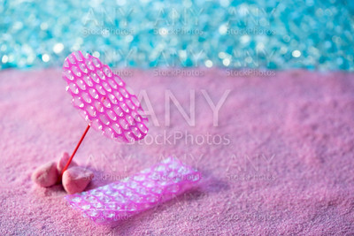 Beach vacation concept pink sand parasol