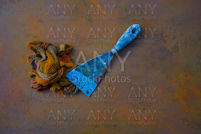 Spatula and colorful rag on oxide background