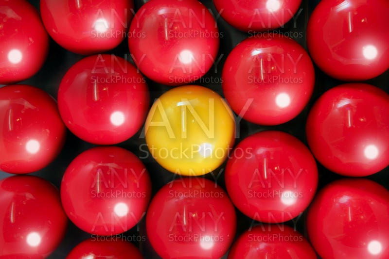 Alone billiard yellow ball between many red balls