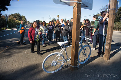 Mother Rosalina Enciso lays flowers at a ghost bike  during a memorial ceremonty held at the site of the death of Jose Enciso Hernandez, 26, who was struck in October by a car on Tennyson Road near the Interstate 880.