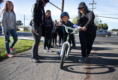 Aiden Cotter, 9,  tries to ride a bike at Weekes Community Park in Hayard and is asisted by America Enciso, before heading out to the site of the hit and run site. They are  respectively nephew and cousin of Jose Enciso Hernandez, 26, who was struck in October by a car on Tennyson Road near the Interstate 880 on-ramp and died.  At left is Gabriela Lopez, sister, Yessenia Lopez, cousin, Guadalupe Lopez, cousin. Photo by Paul Kuroda