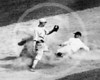 Baseball player sliding into base as fielder reaches to apply tag during baseball game 1910.