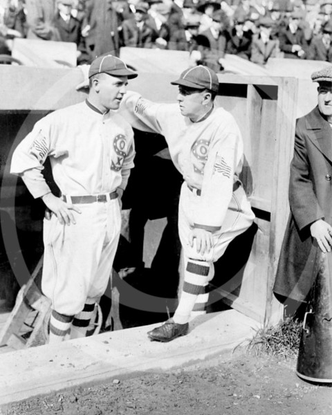 Clarence Pants Rowland, manager of the Chicago White Sox AL, right, talks with his pitcher, Eddie Cicotte, left, in the dugout during a game 1917.