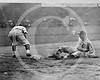 Detroit Tigers AL player slides safely into third base as a Washington Senators AL fielder reaches to the left for ball on the ground during a baseball game 1910.
