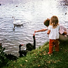 """Barbara and Michelle feeding ducks in Karls-Aue, a park in downtown Kassel. Micky is a little girl we took care of for three or four days while her mother was in the hospital."" German, 1967"