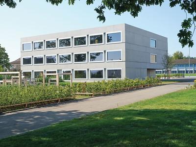 01 Das neue Schulhaus markiert den Zugang zum Schulcampus.