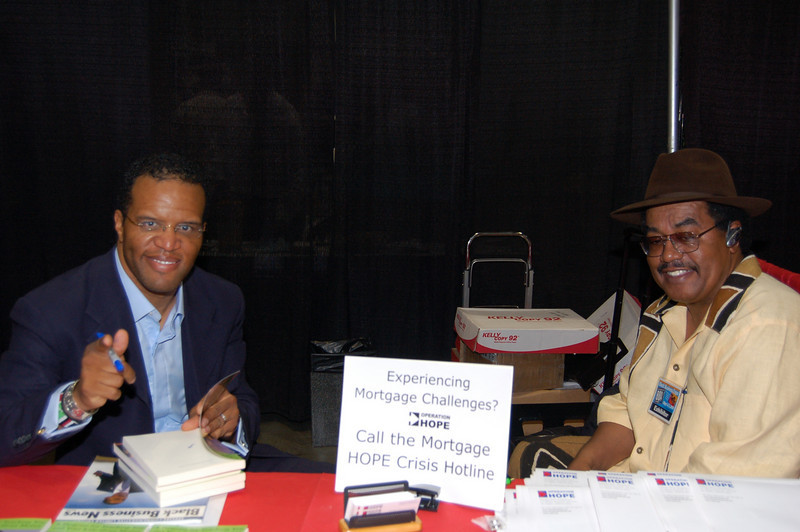 """World traveler John Hope Bryant signs his new book while Black Business Association head Earl """"Skip"""" Cooper visits his booth. <br /> <br /> Photo by Isidra Person-Lynn"""