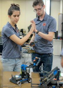 Brittany Coito, left and Jacob De Necorhea high five as BCOE representatives compete with newly purchased robots as they learn how things work before teaching students how to use them during this coming school year Friday Aug. 3, 2018.  (Bill Husa -- Enterprise-Record)