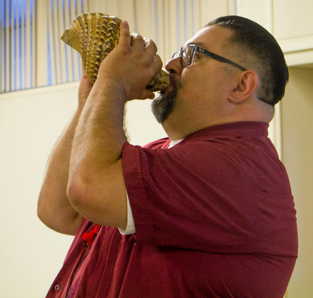 Sean Arce calls in the four directions in a Mesoamerican ceremony that uses a conch shell.