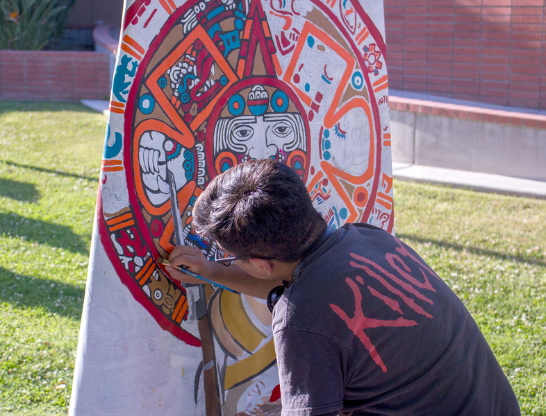 A BC student paints an Aztec mural in the Administration courtyard.