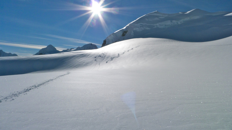 We shared the hut with two Australians seen here telemark skiing.  The thin shadow line above the rollover is the only visible sign of the crevasse Rob discovered that morning.