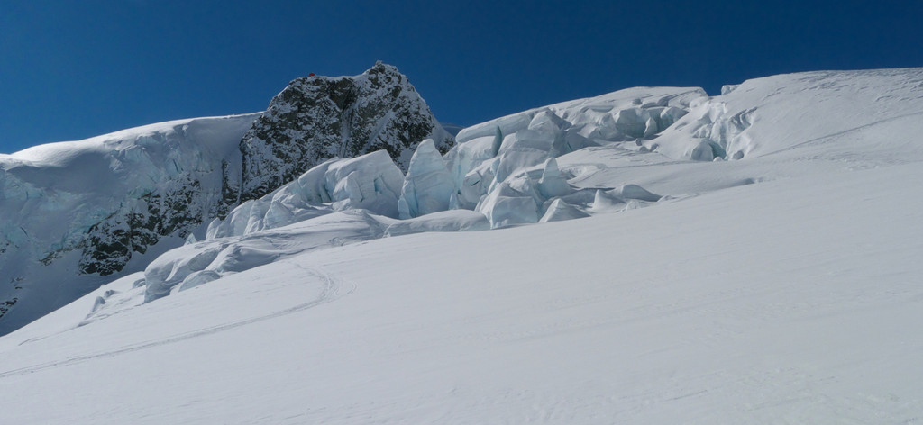 Ski tracks (not ours) emerging from a field of seracs.  Tasman Saddle Hut is perched on the cliff above.